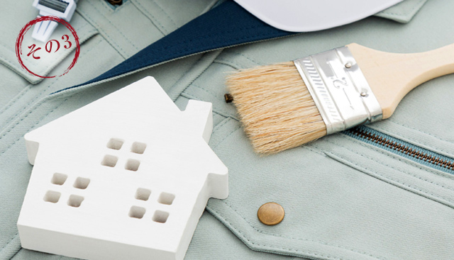 岡崎市で外壁塗装をお考えなら | 作業服の上に置かれたハケと家のおもちゃ